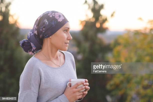 Ethnic woman battling cancer stands outside and contemplates her life