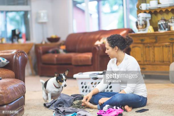 Ethnic woman in her 20s folds laundry on the living room floor while her adorable dog keeps her company