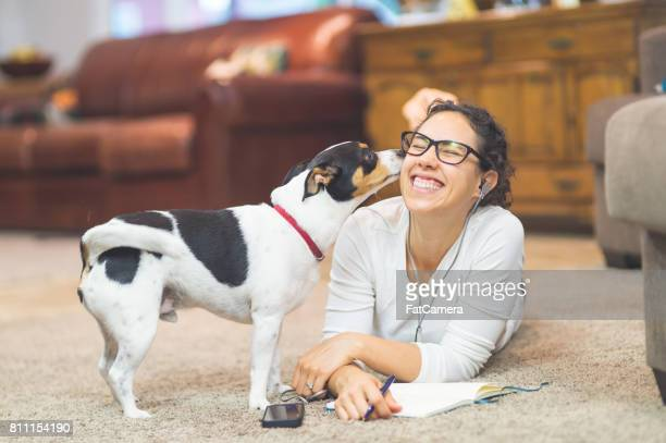 Ethnic woman in her 20s plays with dog on living room floor