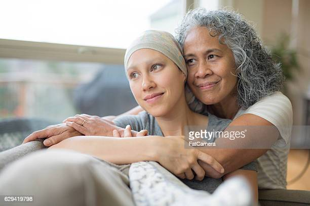 Ethnic young adult female cancer patient hugged by her mother