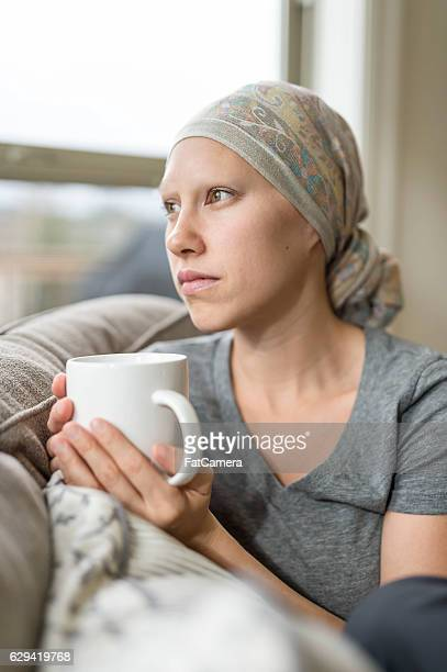 ethnic young adult female cancer patient sipping tea and contemplating - tumeur nez photos et images de collection