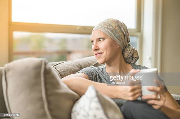 ethnic young adult female cancer patient sipping tea - completely bald stock pictures, royalty-free photos & images