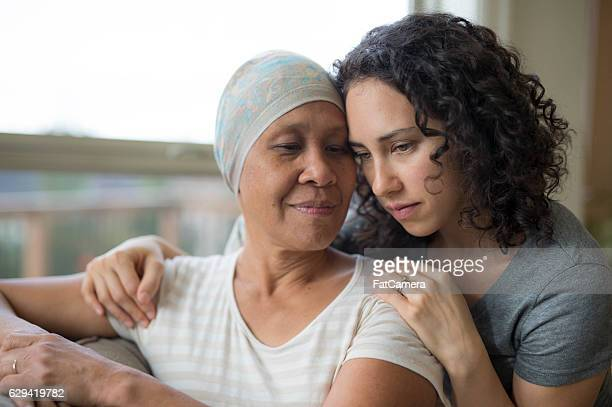 Ethnic young adult female hugging her mother who has cancer