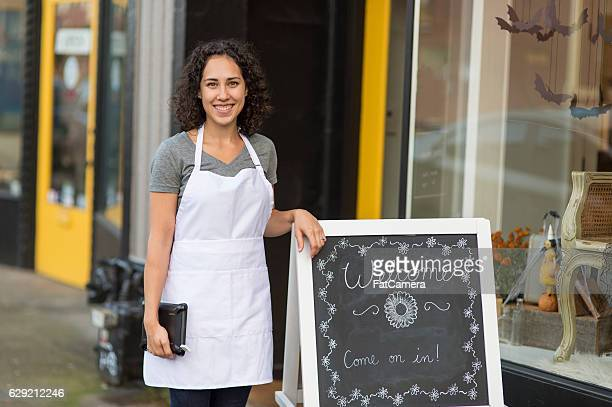 Ethnic young adult female standing outside her small business
