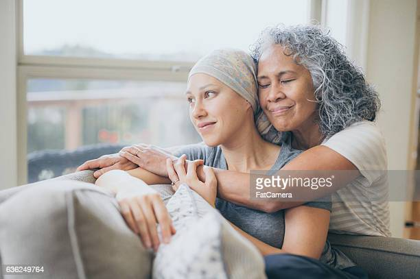 Ethnic young adult female with cancer being embraced