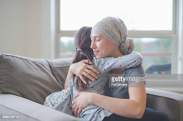 ethnic young adult female with cancer hugging her daughter - bald woman stock photos and pictures