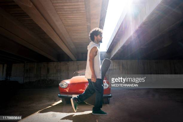 ethnic young guitar man walking to  rehearsal - grimes musician stock pictures, royalty-free photos & images
