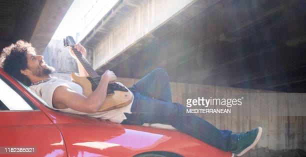 ethnic young guitar player sitting on red generic car - modern rock stock pictures, royalty-free photos & images