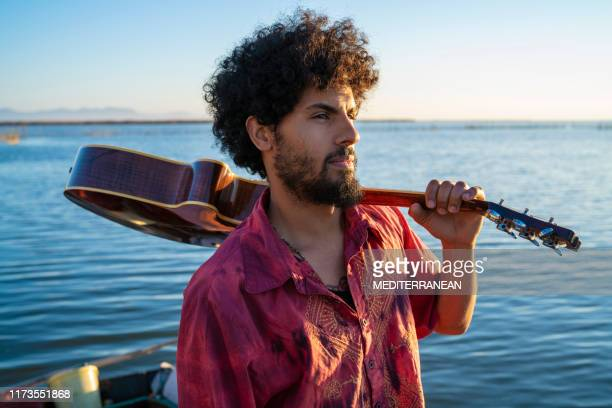 ethnic young man holding guitar on the lake shore - stars and strings 2019 stock photos and pictures