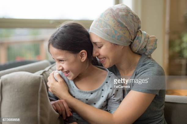 ethnic young mom with cancer holding daughter - cancer stock photos and pictures