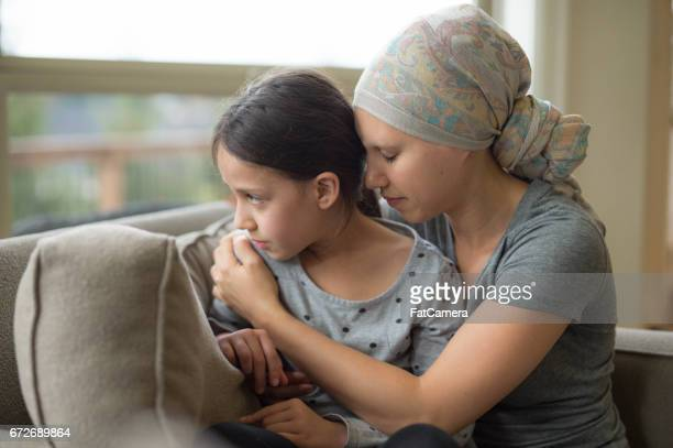 Ethnic young mom with cancer holding daughter