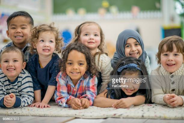ethnically diverse group of kids smiling portrait - preschool stock pictures, royalty-free photos & images
