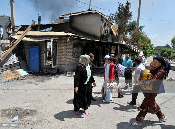 Ethnik Uzbeks gather near their burned out homes in Osh on June 14, 2010. Deadly gun battles raged in the Kyrgyzstan city of Osh where bodies...