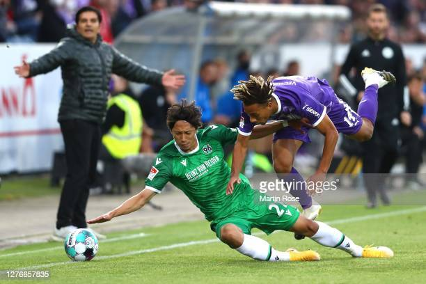 Etienne Amenydo of Osnabrück battles for the ball with Sei Muroya of Hannover during the Second Bundesliga match between VfL Osnabrück and Hannover...