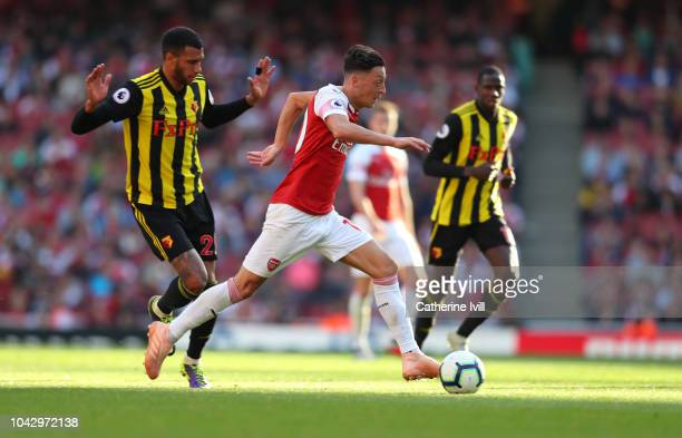 Etienne Capoue of Watford and Mesut Ozil of Arsenal during the Premier League match between Arsenal FC and Watford FC at Emirates Stadium on...