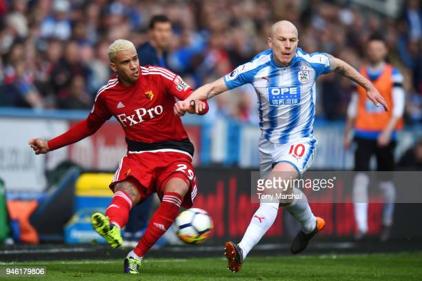 Etienne Capoue of Watford crosses the ball under pressure from Aaron Mooy of Huddersfield Town during the Premier League match between Huddersfield...