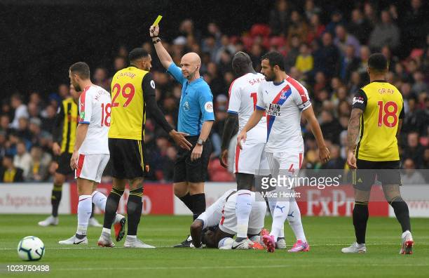Etienne Capoue of Watford is shown a yellow card by referee Anthony Taylor during the Premier League match between Watford FC and Crystal Palace at...
