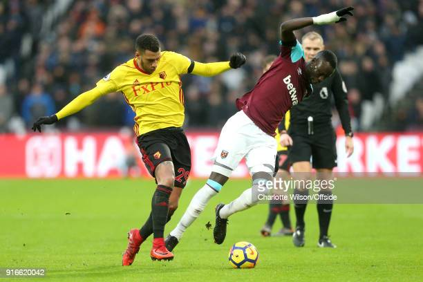 Etienne Capoue of Watford pushes Cheikhou Kouyate of West Ham as they battle for the ball during the Premier League match between West Ham United and...