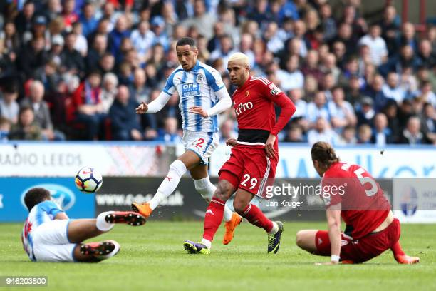 Etienne Capoue of Watford shoots under pressure from Tom Ince of Huddersfield Town during the Premier League match between Huddersfield Town and...