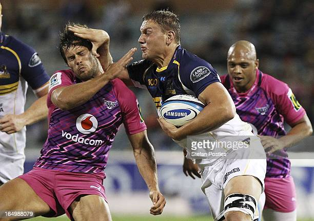 Etienne Oosthuizen of the Brumbies fends off Jan Serfontein of the Bulls during the round seven Super Rugby match between the Brumbies and the Bulls...