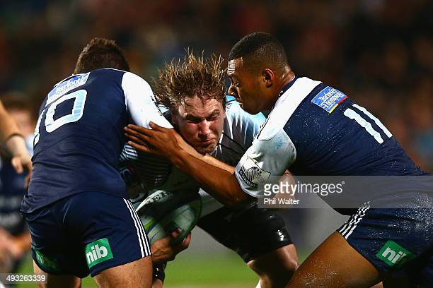 Etienne Oosthuizen of the Sharks is tackled by Simon Hickey and Tevita Li of the Blues during the round 15 Super Rugby match between the Blues and...