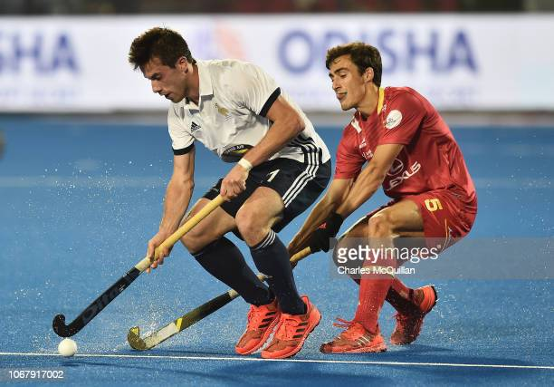 Etienne Tynevez of France controls the ball as Marc Serrahima of Spain looks on during the FIH Men's Hockey World Cup Pool A match between Spain and...
