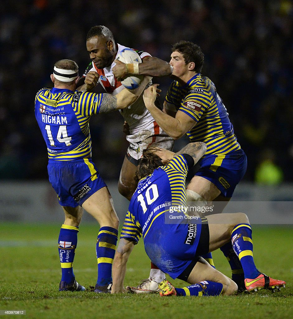 Eto Nabuli of St George Illawarra Dragons is tackled by Micky Higham and Ashton Sims of Warrington Wolves during the World Club Series match between Warrington Wolves and St George Illawarra Dragons at The Halliwell Jones Stadium on February 20, 2015 in Warrington, England.