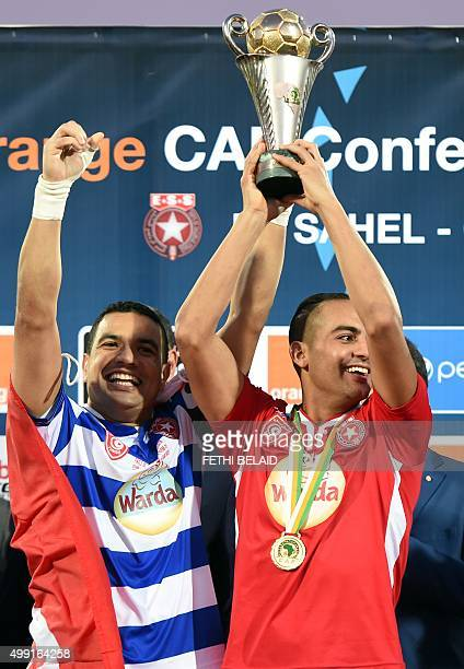Etoile du Sahel captain Aymen Mathlouthi and Ammar Jemal scorer of the winning goal pose with the CAF trophy after defeating the Orlando Pirates...