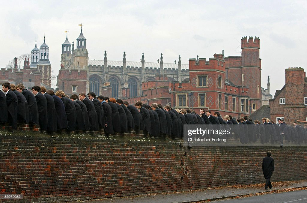 Eton boys, perched on the wall, watch the tradtional wall game on November 17, 2007 in Eton, England. The game which is unique to Eton, is played between the 'Collegers' and the 'Oppidans' and is a complex mixture of rugby and football, played on a narrow pitch against a 110 metre long brick wall. The objective of the game is to manoeuvre the ball the length of the wall to enable a scoring opportunity, a relatively rare occurrence.