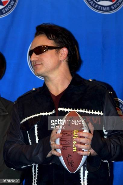 ETrade Super Bowl XXXVI Halftime Show news conference featuring the Legendary Rock Band U2 with Bono Bono holding NFL football with both handssaid...