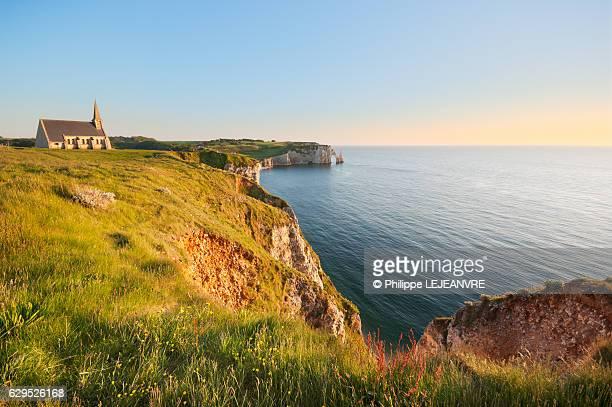 Etretat cliffs and Notre-Dame de la garde chapel at sunset - Normandy