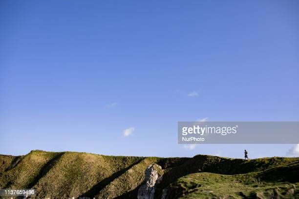 Etretat Normandy France March 25 2019 A woman walks alone on the aval cliff in good weather Etretat Normandie France le 25 mars 2019 Une femme marche...