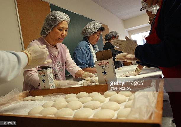 Etsuko Heatley Angie Tsuneyoshi and other women form cooked and pounded rice into small cakes as they participate in making Japanese rice cakes...