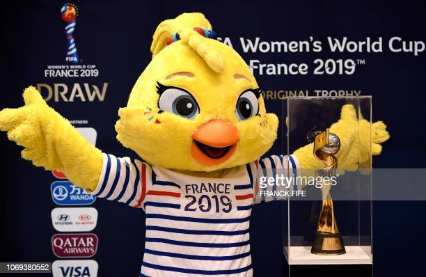 Ettie the mascot of the 2019 FIFA Womens World Cup is presented next to the competition's trophy on December 7 2018 in BoulogneBillancourt near Paris