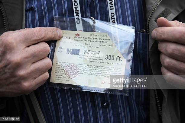 Ettore Garofalo, a survivor of the Heysel tragedy, shows his ticket from the match ahead of a mass at Gran Madre di Dio church in Turin on May 29 to...