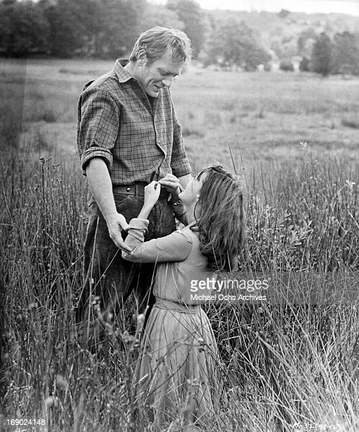 Ettore Manni and Jeanne Moreau standing romantically together in the field in a scene from the film 'Mademoiselle', 1966.