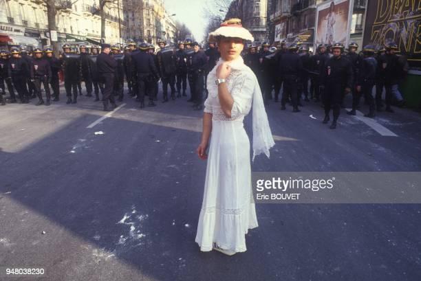 Etudiant deguise en jeune femme romantique lors du defile de Mardi Gras avec a l'arriere-plan un mur de policiers le 6 mars 1984 a Paris, France.