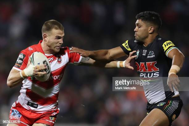 Euan Aitken of the Dragons hands off Tyrone Peachey of the Panthers during the round 12 NRL match between the Penrith Panthers and the St George...