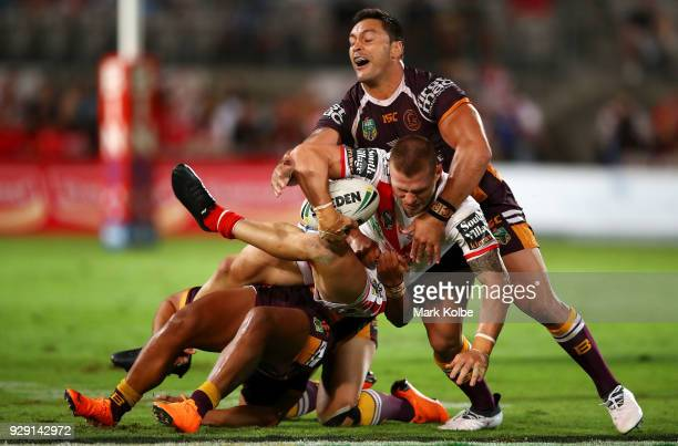 Euan Aitken of the Dragons is tackled Alex Glenn of the Broncos during the round one NRL match between the St George Illawarra Dragons and the...