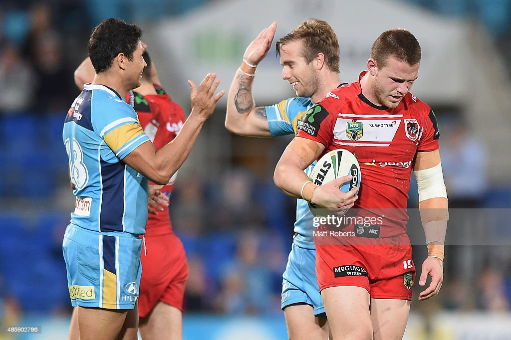 Euan Aitken of the Dragons looks dejected as Brad Tighe and Kane Elgey of the Titans celebrate victory during the round 25 NRL match between the Gold Coast Titans and the St George Illawarra Dragons at Cbus Super Stadium on August 30, 2015 on the Gold Coast, Australia.