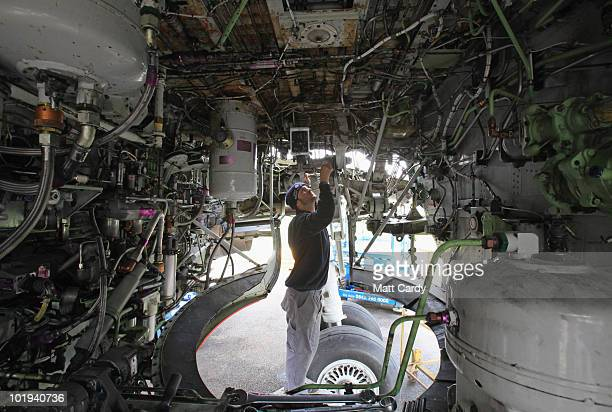 Euan White removes parts of the fuel system in the wheel well of a 737 600 currently being dismantled on June 9, 2010 in Kemble, England. The...