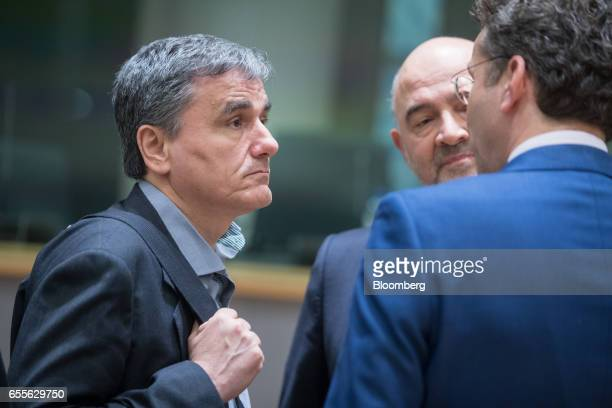 Euclid Tsakalotos Greece's finance minister left speaks with Pierre Moscovici economic commissioner for the European Union center and Jeroen...