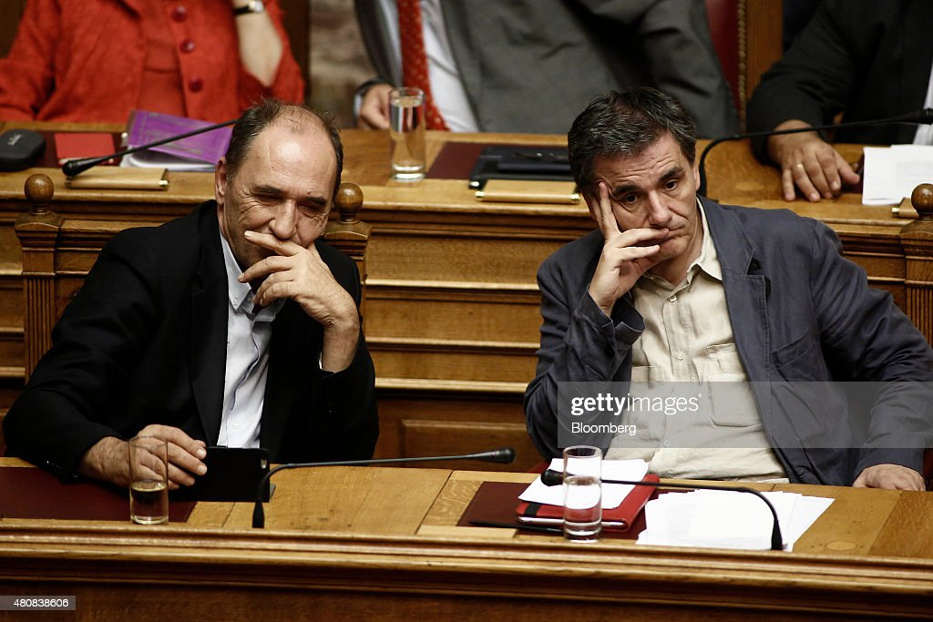 Euclid Tsakalotos, Greece's finance minister, right, and George Stathakis, Greece's economy minister, look on before a parliamentary vote on whether to accept bailout conditions in Athens, Greece, on Wednesday, July 15, 2015. Greek lawmakers passed a bailout agreement that keeps the country in the euro for now, shifting attention to the European Central Bank as it weighs whether to pump more money into the country's hobbled financial system. Photographer: Kostas Tsironis/Bloomberg via Getty Images