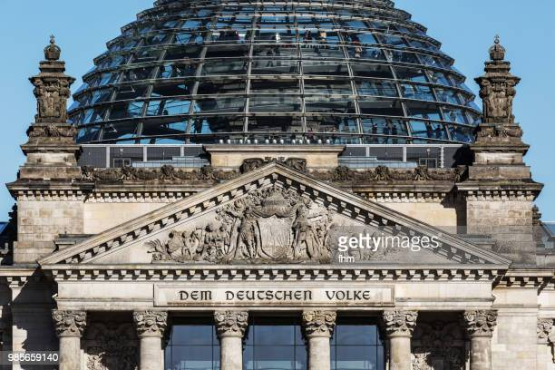 EU-flag with the famous inscription on the architrave on the west portal of the Reichstag building in Berlin: 'Dem Deutschen Volke' with dome (Berlin, Germany)