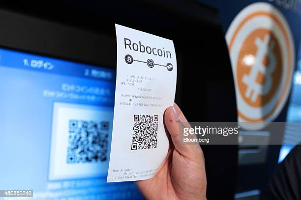 Eugene Aono a spokesperson for BMEX bitcoin exchange holds a receipt displaying a quick response code for a photograph while demonstrating usage of...