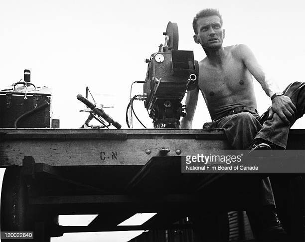 Eugene Boyko cameraman with a camera and other film equipment by his side sits on a Canadian National Railways railroad trolley during the National...