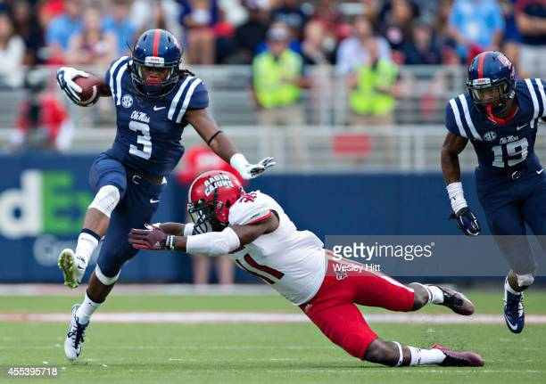 Eugene Brazley of the Ole Miss Rebels tries to avoid the tackle of Jevante Watson of the LouisianaLafayette Ragin' Cajuns at VaughtHemingway Stadium...