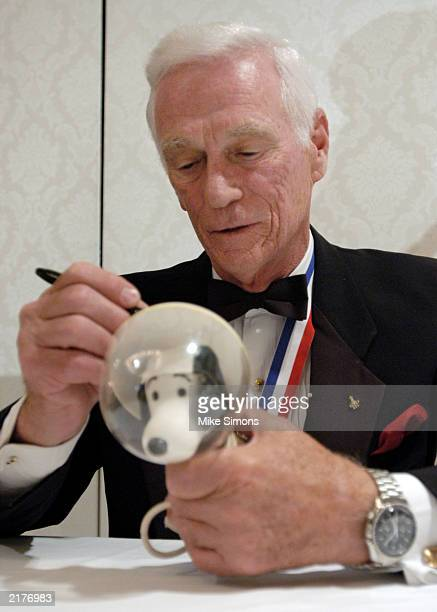 Eugene Cernan an astronaut on NASA's Gemini IX mission signs a space suit wearing Snoopy doll after a press conference July 19 2003 in Dayton Ohio...
