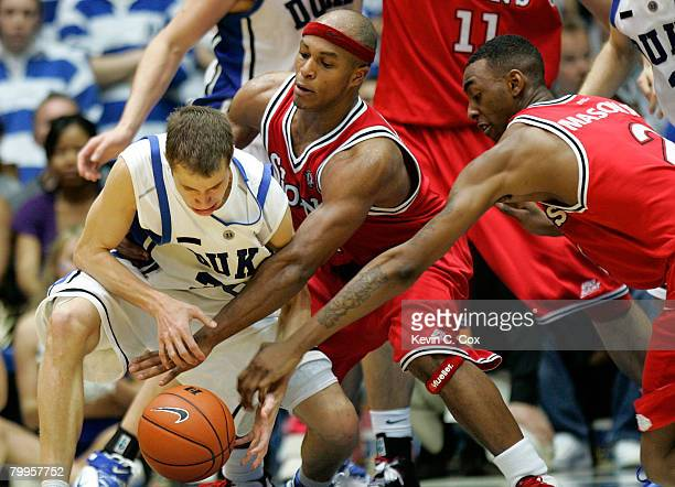 Eugene Lawrence and Anthony Mason Jr. #2 of the St. John's Red Storm reach for a steal against Jon Scheyer of the Duke Blue Devils during the second...