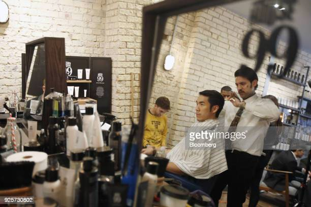 Eugene Lee Yang, writer, director, producer and lifestyle blogger, is reflected in a mirror as he has his hair styled by barber Fabio Marques during...